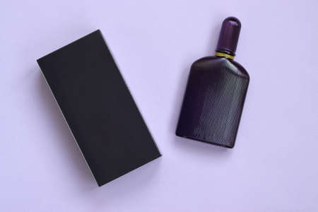 Dark purple perfume bottle with golden ribbon on pastel paper background. Trendy fragrance design