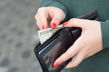 Woman hands with red nails holds black mens purse with many US hundred dollars bills. Concept of salary earnings or money counting