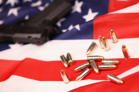 Many yellow 9mm bullets and gun on United States flag. Concept of gun trafficking on USA territory or US shooting range