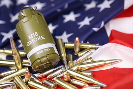 M18 smoke grenade and many yellow bullets and cartridges on United States flag. Concept of gun trafficking on USA territory or special operations