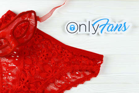 KHARKOV, UKRAINE - FEBRUARY 14, 2021: Onlyfans paper logo and red lingerie. OnlyFans is content subscription service based in London, United Kingdom