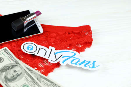 KHARKOV, UKRAINE - FEBRUARY 14, 2021: Onlyfans paper logo with dollar bills, red lipstick with smartphone and red lingerie on white wooden table. OnlyFans is content subscription service Redakční