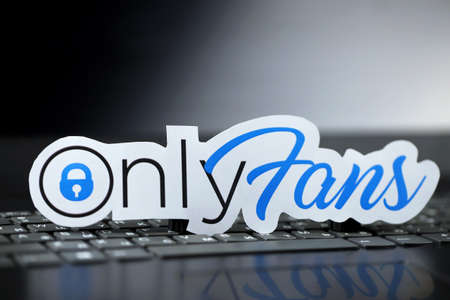 KHARKOV, UKRAINE - FEBRUARY 14, 2021: Onlyfans paper logo on black laptop keyboard. OnlyFans is content subscription service based in London, United Kingdom