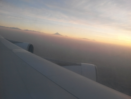 aerial view of damavand mountain along horizon and sunset and airplane wing Lizenzfreie Bilder