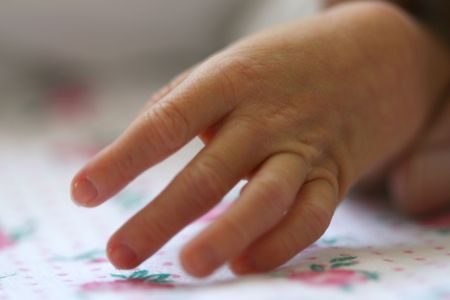Baby holding mothers finger photo