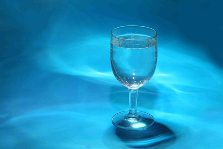 Glass of water and ice on a blue background  photo