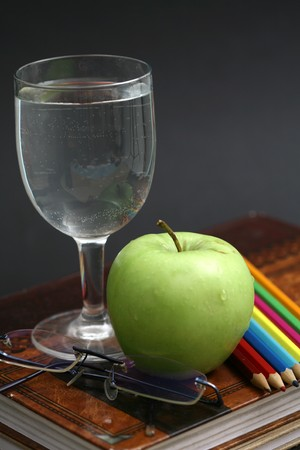 green apple resting on the book with chalk board as background  photo