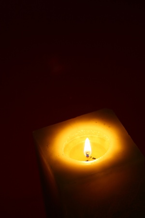 Close-up candle illuminates the darkness of the night environment Stock Photo