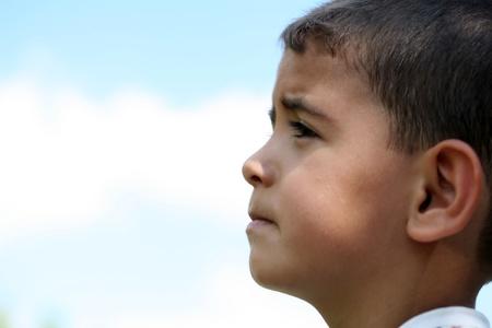 bambini pensierosi: Un ragazzino triste su sfondo blu Archivio Fotografico