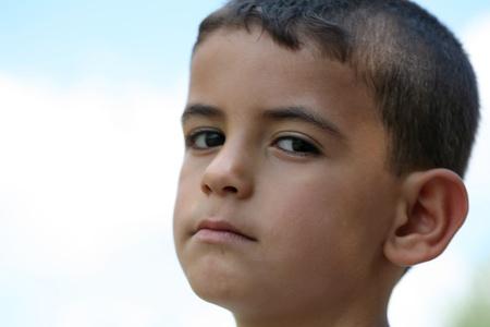 A sad little boy on a blue background  Stock Photo