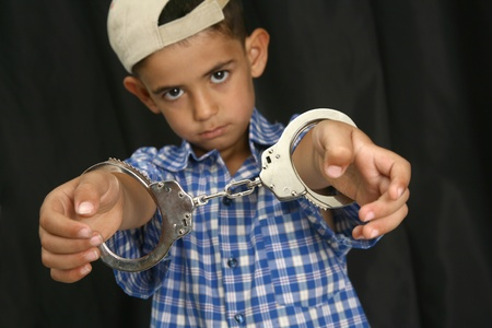 Young kid with steel-cuffs bonded Stock Photo - 10366373
