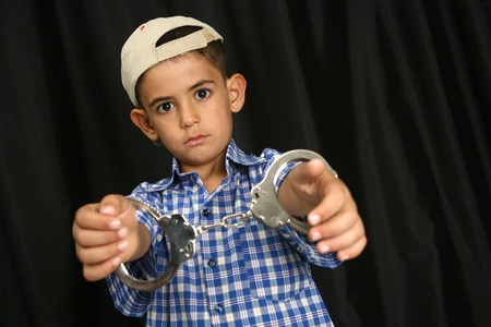 Young kid with steel-cuffs bonded Stock Photo - 10366392