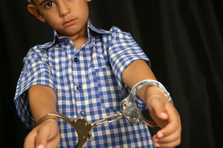 criminal law: Young kid with steel-cuffs bonded