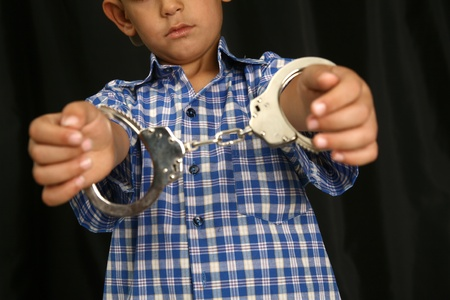 Young kid with steel-cuffs bonded Stock Photo - 10366409