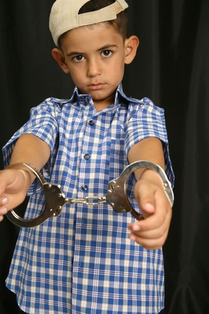 Young kid with steel-cuffs bonded Stock Photo - 10366408