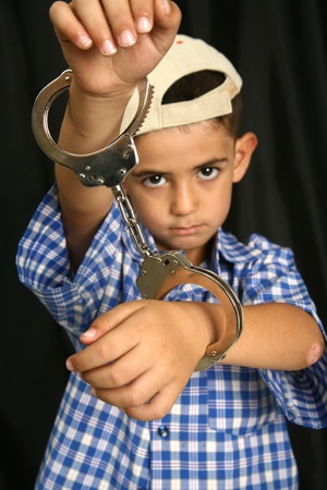 Young kid with steel-cuffs bonded Stock Photo - 10366390