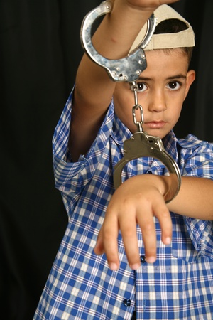 Young kid with steel-cuffs bonded Stock Photo - 10366405