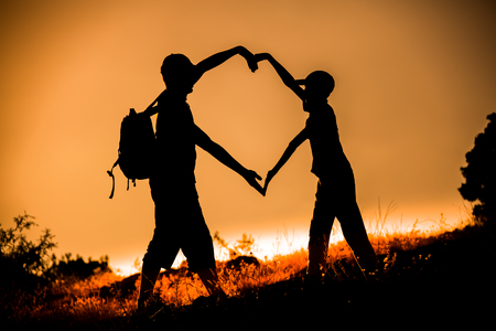 forming: Silhouetted friend forming a heart symbol at golden hour sunset Stock Photo
