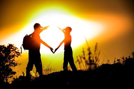position d amour: ami Silhouetted formant un symbole de coeur au coucher de soleil d'or de l'heure Banque d'images