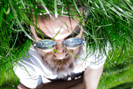 Man who looks upside down in the green of spring
