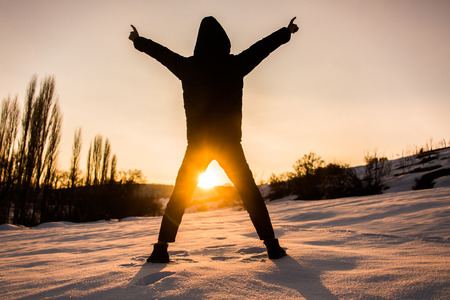The silhouette of a young boy at sunset in winter Stock Photo