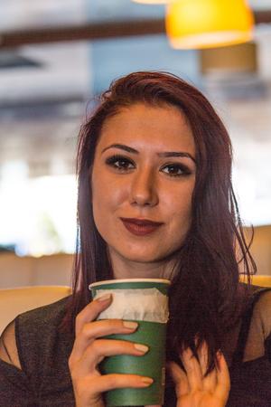 Beautiful girl drinking coffee at the coffee shop