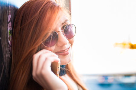 A beautiful girl wearing sunglasses talking on the phone and smiling Stock Photo