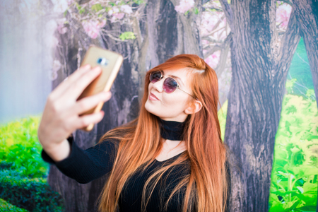 A beautiful girl wearing sunglasses taking a selfie with a smartphone Stock Photo