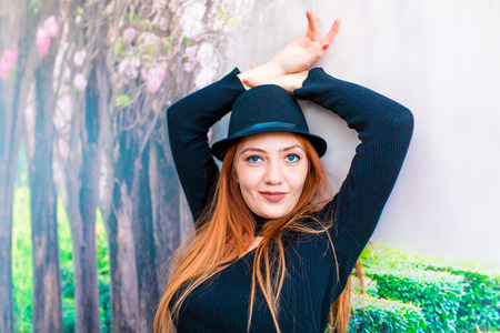 A beautiful blonde girl in black dress and a hat posing Stock Photo