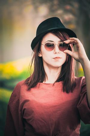 A beautiful girl wearing sunglasses and a hat posing Banco de Imagens