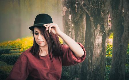 A beautiful girl wearing a black hat posing Banco de Imagens