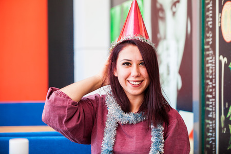 A beautiful girl wearing a party hat smiling Stock Photo