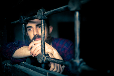 a helpless prisoner between the bars Stock Photo