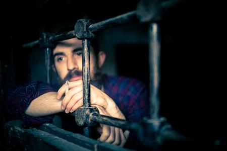 a helpless prisoner between the bars Stock Photo