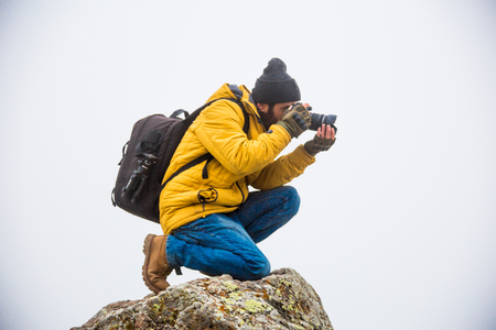 A man taking a photograph on top of a mountain Stok Fotoğraf