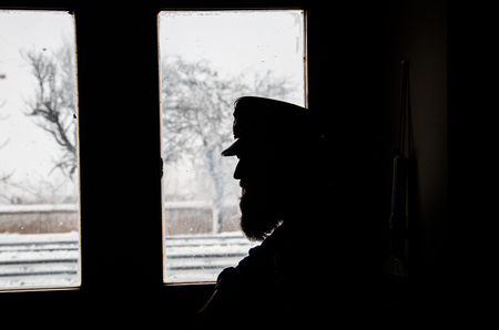 silhouette image of station attendant looking at window