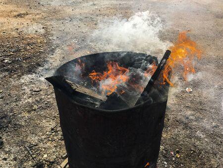 Burning wood fire in oil barrel in industry Фото со стока