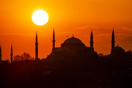 Cityscape of Istanbul with silhouettes of ancient mosques and minarets at sunset. Panoramic view, The Maidens Tower, Galata Tower, Hagia Sophia, The Blue Mosque and Topkapı Palace in Istanbul.
