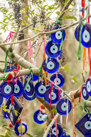 The branches of the old tree decorated with the eye-shaped amulets - Nazars, made of blue glass and believed to protect against the evil eye in Goreme national park, Cappadocia, Turkey.
