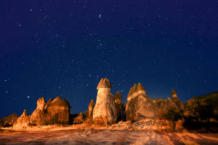 Volcanic rock formations known as fairy chimneys at night with stars in the sky, Cappadocia, Turkey