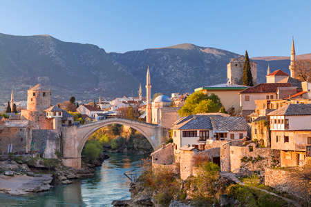 Skyline of Mostar with the Mostar Bridge, houses and minarets, at the sunset in Bosnia and Herzegovina