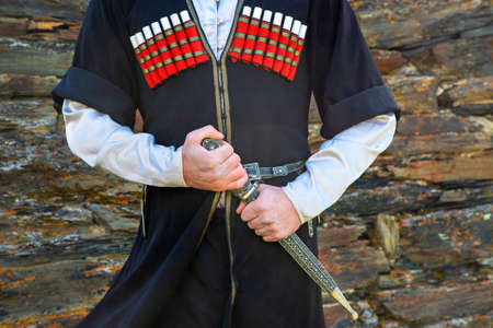 Georgian man in traditional clothes holding the dagger, Caucasus Mountains, Georgia