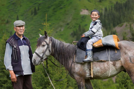 Kazakh man with his grandson on the horse, Kazakhstan.