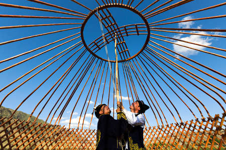 Kazakh men build a yurt and hold the crown of the dome in Saty Village, Kazakhstan Editorial
