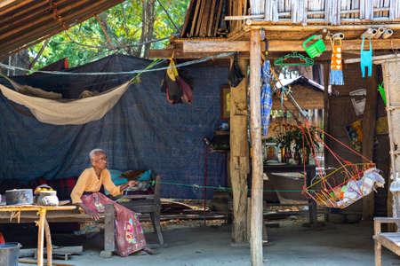 Elderly woman swings the baby cradle, in Bagan, Myanmar