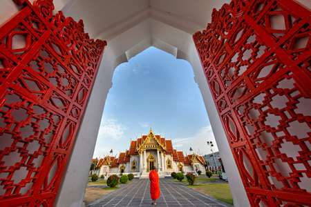 Buddhist Marble Temple known also as Wat Benchamabopit Dusitvanaram with a monk walking in the garden, Bangkok, Thailand. Stockfoto