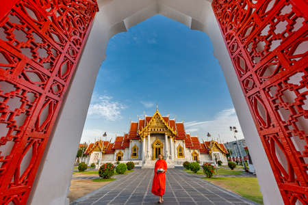 Buddhist Marble Temple known also as Wat Benchamabopit Dusitvanaram with a monk walking in the garden, Bangkok, Thailand. Redactioneel