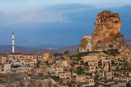 View over the ancient houses and cave dwellings in the town Ortahisar with snow capped volcano Erciyes in the background, Cappadocia, Turkey Stock Photo