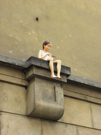 A statue of a little girl on the ledge of a building in Old Prague.