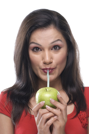 sipping: Woman sipping juice Stock Photo